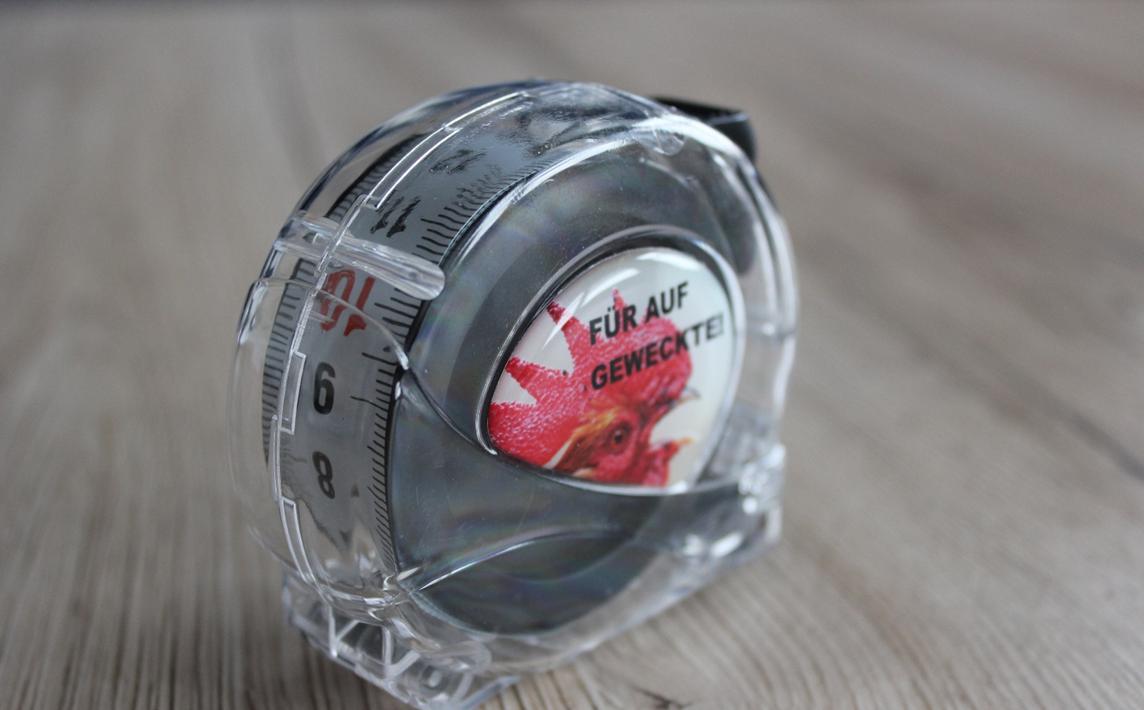 Ein Rollbandmaß als optisches Highlight im komplett durchsichtigen Kunststoffgehäuse - Nylonmaßband beidseitig 1x Horzinzontalmessung, 1 x Vertikalmessung - veredelbar mit Ihrem Doming